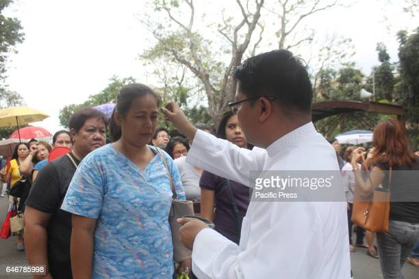 Catholic seminarian puts ashes on a woman's forehead during Ash Wednesday at the National Shrine of Our Mother of Perpetual Help in Parañaque City...