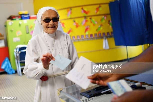 A Catholic Sister votes at a polling station in Nantes western France during the second round of the French parliamentary elections on June 18 2017 /...