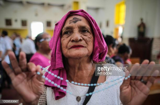 Catholic woman holds a rosary during the celebration of Ash Wednesday at the Cathedral in Managua on February 26 2020 Ash Wednesday initiates Lent...