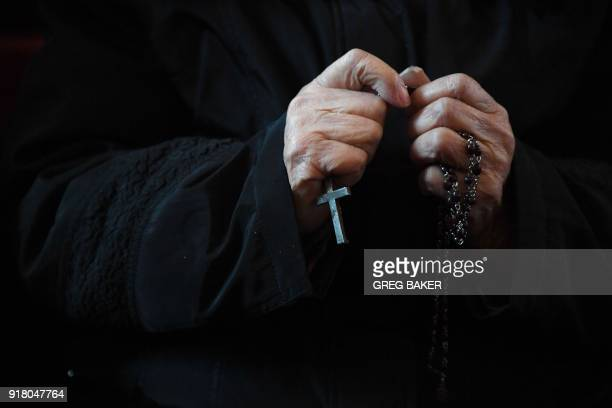 A Catholic worshipper holds a cross during an Ash Wednesday mass which marks the beginning of Lent at Beijing's government sanctioned South Cathedral...
