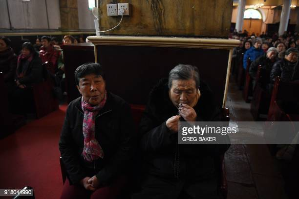 A Catholic worshipper kisses a cross during an Ash Wednesday mass which marks the beginning of Lent at Beijing's government sanctioned South...
