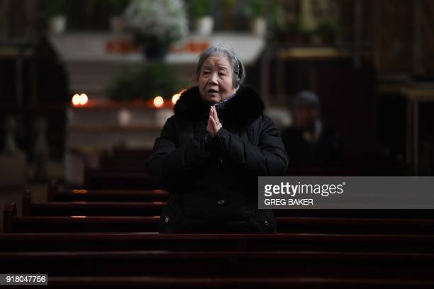 A Catholic worshipper prays after an Ash Wednesday mass which marks the beginning of Lent at Beijing's government sanctioned South Cathedral on...