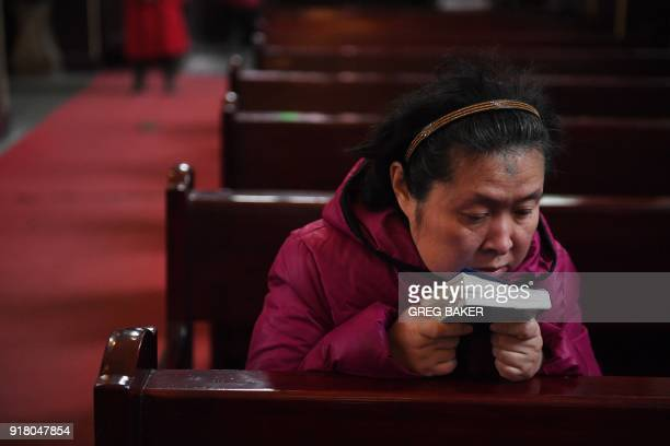 A Catholic worshipper reads after mass on Ash Wednesday which marks the beginning of Lent at Beijing's government sanctioned South Cathedral on...