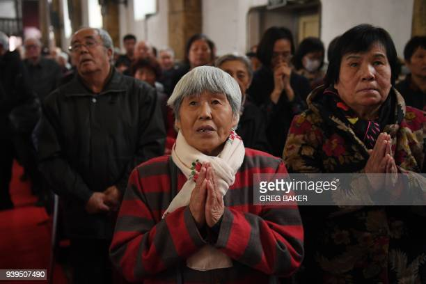 Catholic worshippers attend mass on Holy Thursday, ahead of Easter celebrations at Beijing's government sanctioned South Cathedral in Beijing on...