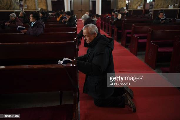 Catholic worshippers perform ceremonies on Ash Wednesday which marks the beginning of Lent at Beijing's government sanctioned South Cathedral on...