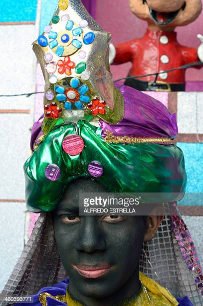 A Catholic young boy dressed as 'Balthazar' poses before a representation of the Three Wise Men at Mexico City's Buenavista neighbourhood before a...