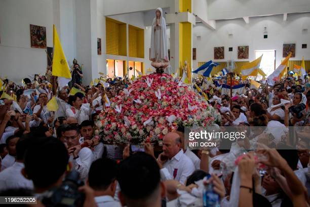 Catholics carry the image of the Virgin of Fatima inside the Cathedral in Managua on January 25 after its arrival from Portugal