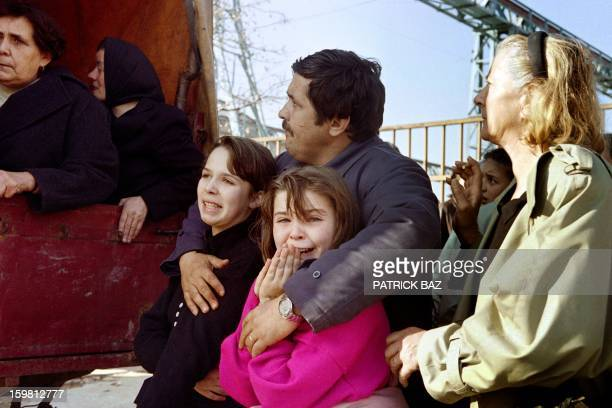 Catholics girls cry in their father's arms after they were stopped on their way out by a Bosnian Military Police road-block and forbidden to leave...