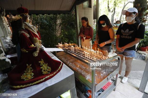 Catholics go through containment protocols including body-temperature measurement and hands-sanitisation before entering the Saint Christopher Parish...