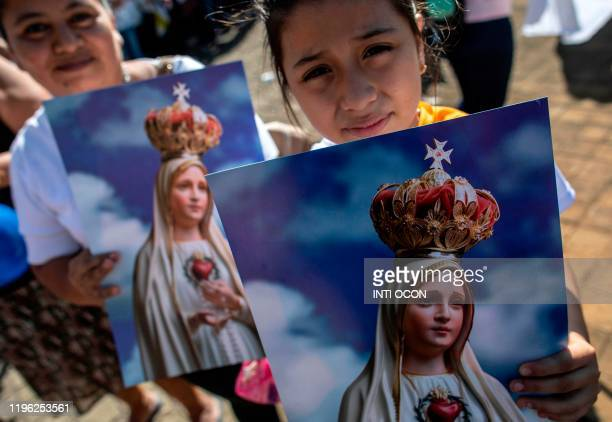 Catholics hold posters as the image of the Virgin of Fatima arrives from Portugal to the Cathedral in Managua on January 25 2020