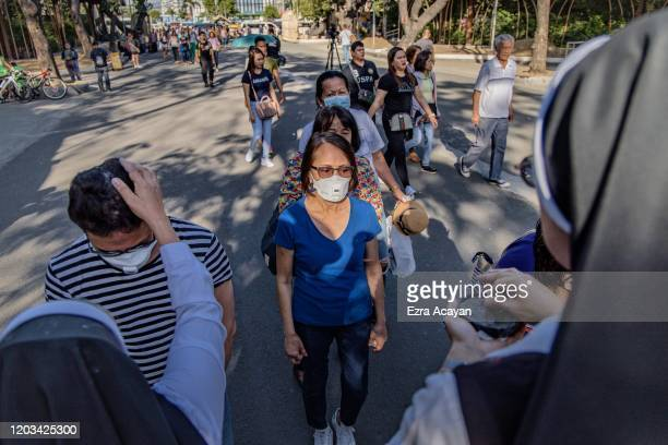 Catholics nuns sprinkle ash on the heads of devotees during Ash Wednesday services at a church on February 26 2020 in Paranaque city Metro Manila...