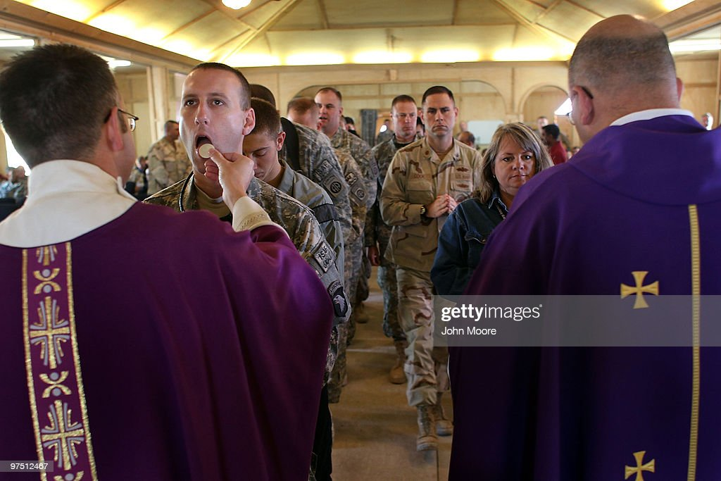 Catholics partake in Communion at a Catholic Mass on March 7, 2010 in Kandahar Air Field in southern Afghanistan. Military chaplains hold services on major bases as well as travel the battlefield throughout Afghanistan, providing a backbone of support for thousands of soldiers struggling with the difficulties of war and year-long deployments away from home.