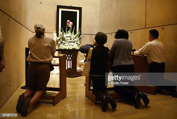 Catholics pray next to a photograph of Pope John Paul II at Our Lady of Angels cathedral April 2 2005 in Los Angeles California