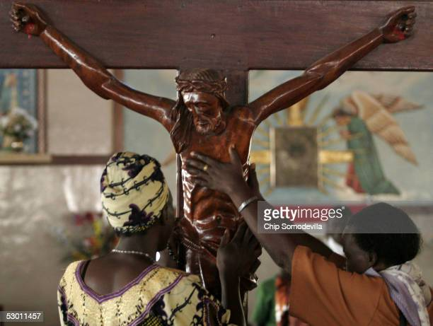 Catholics reach to touch a wood crucifix at the Catholic Basilica Church of the Uganda Martyrs a day before the Ugandan national Martyrs Day holiday...