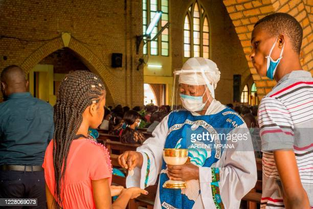 Catholics receive the Holy Communion during the service at the Notre Dame du Congo cathedral in Kinshasa on August 16, 2020 where the Holy Mass is...