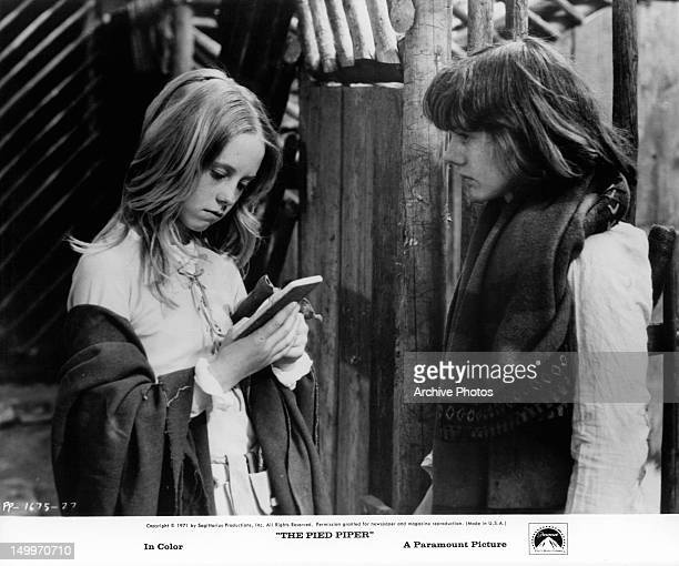 Cathryn Harrison reading notebook with Jack Wild standing by in a scene from the film 'The Pied Piper' 1972