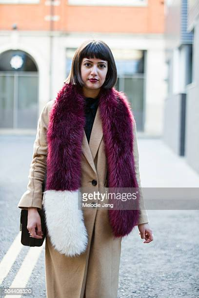 Cathy Bhairo wears a camel Topshop coat a maroon and white fur shawl and Nike Air Huarache floral sneakers during The London Collections Men AW16 on...