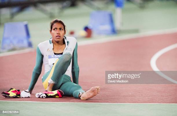 Cathy Freeman of Australia sits on the track following her victory in the Women's 200 meter event of the 2000 Summer Olympics track and field...