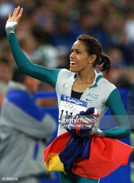 Cathy Freeman of Australia waves to the crowd holding teh Australian and Aboriginal flags after winning the Olympic gold in the 400m final 25...