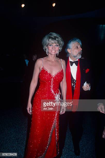 Cathy Lee Crosby wearing a red beaded gown with a friend in a tux circa 1970 New York