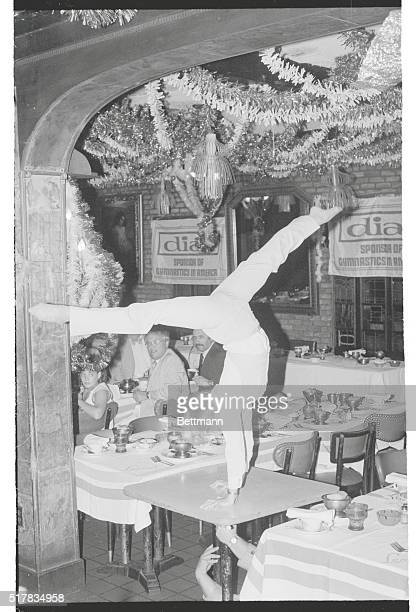Cathy Rigby in a handstand pose atop a dining room table at a press conference sponsored by Dial Soap July 1979