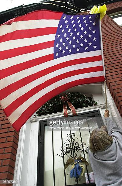 Cathy Ryan hangs an American flag with a yellow ribbon tied to it by the front door of her house in Carroll Gardens Brooklyn in honor of the American...