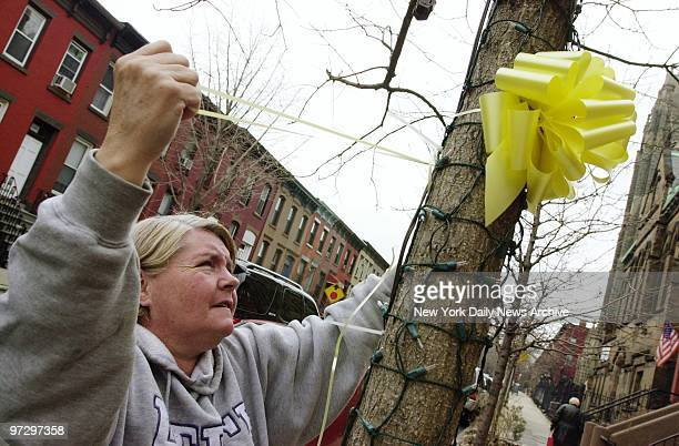 Cathy Ryan ties a yellow ribbon around a tree in front of her house in Carroll Gardens Brooklyn in honor of the American troops fighting in the war...