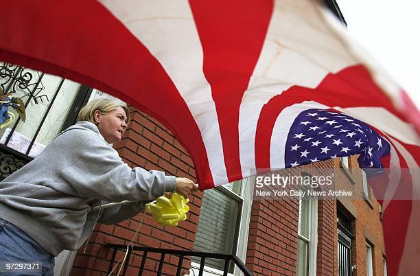 Cathy Ryan ties a yellow ribbon around the American flag hanging by the front door of her house in Carroll Gardens Brooklyn in honor of the American...