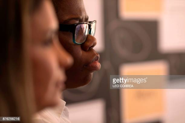 Catia Fernandes product development manager of fashion brand Maria Filo listens an explanation delivered by Esteban Cipriano from the antiracism...