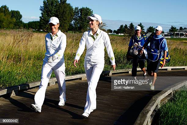 Catriona Matthew and Diana Luna of the European Team walk with their caddies off the first tee during the saturday morning fourball matches at the...