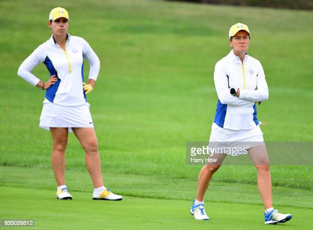 Catriona Matthew and Karine Icher of Team Europe watch a second shot from Team USA on the second hole during the morning foursomes matches of the...