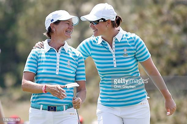 Catriona Matthew of Scotland and Caroline Masson of the European team react after halving their match during the morning Foursome matches for the...