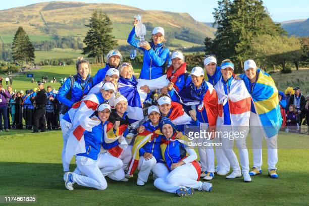 Catriona Matthew the European Team captain is raised high by her team as they pose with teh Solheim Cup after their victory after the final day...
