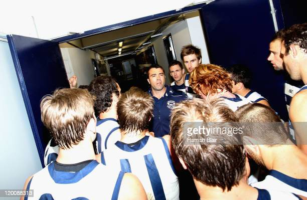 Cats coach Chris Scott addresses the team at the door to the rooms after their victory after the round 19 AFL match between the Geelong Cats and the...