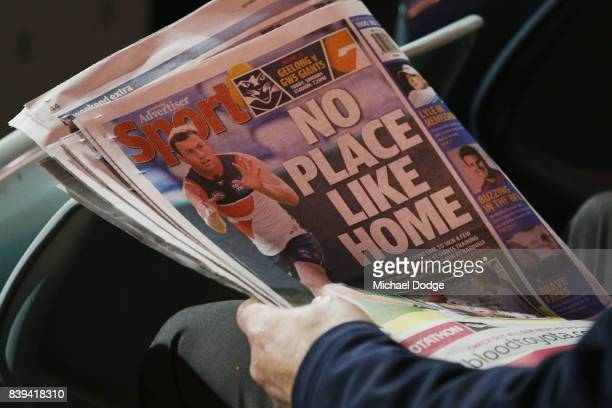 Cats fan reads the local newspaper with former Cats player now Giants player Steve Johnson on the cover during the round 23 AFL match between the...