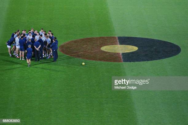 Cats players huddle next to the centre circle with Indigenous colours painted in it as they listen to Cats head coach Chris Scott during the round...