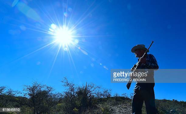 Cattle rancher Jim Chilton holds his rifle while walking across part of his 50000 acre ranch on the USMexico border on October 14 2016 some 20 miles...