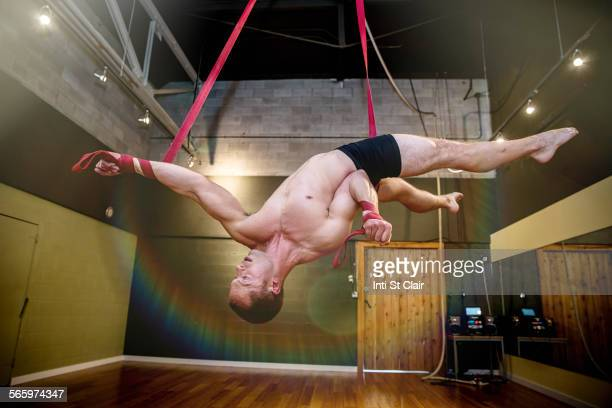 Caucasian acrobat hanging from ropes in studio