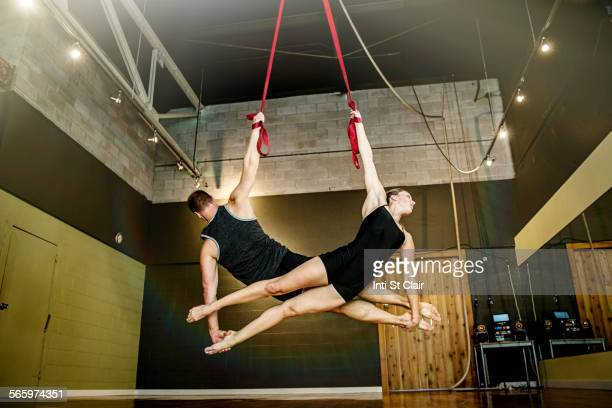 Caucasian acrobats hanging from ropes in studio