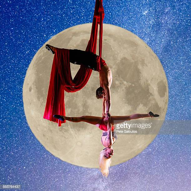 Caucasian acrobats performing with silk ropes by full moon