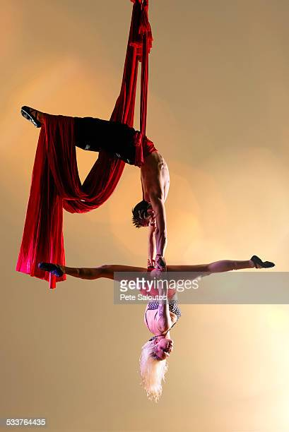 Caucasian acrobats performing with silk ropes