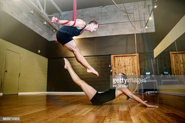 Caucasian acrobats training on ropes in studio