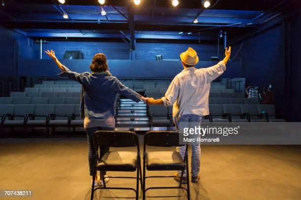 Caucasian actors rehearsing waving in theater