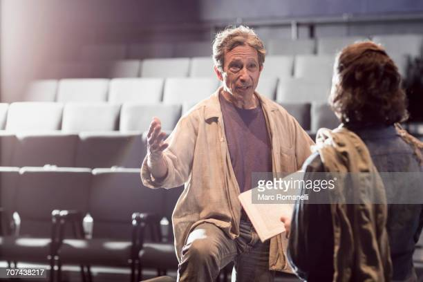 caucasian actors rehearsing with script in theater - rehearsal stock pictures, royalty-free photos & images