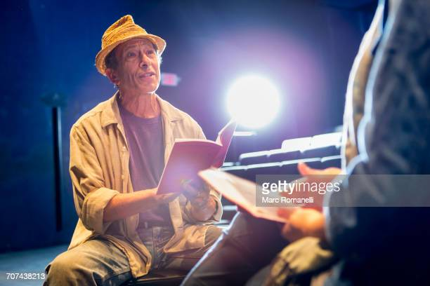 caucasian actors rehearsing with scripts in theater - actor stock pictures, royalty-free photos & images