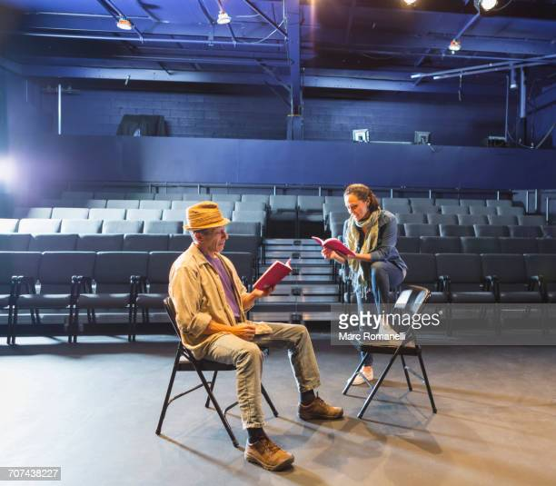caucasian actors rehearsing with scripts in theater - rehearsal stock pictures, royalty-free photos & images