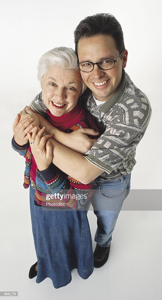 caucasian adult son stands behind and holds gray haired mom while smiling : Foto de stock