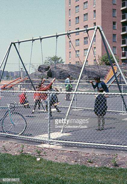 Caucasian and African American children play together on a swing set in a playground outside a public housing project in the Bronx New York City New...