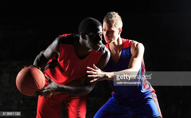 Caucasian and african basketball players on black background