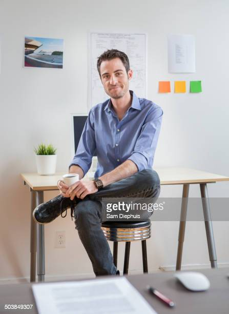Caucasian architect drinking coffee in office